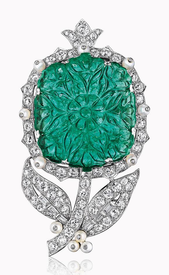 祖母綠、珍珠及鑽石花朵造型胸針,卡地亞設計。此拍品於2016年12月7日在佳士得紐約瑰麗珠寶拍賣中以487,500美元成交。