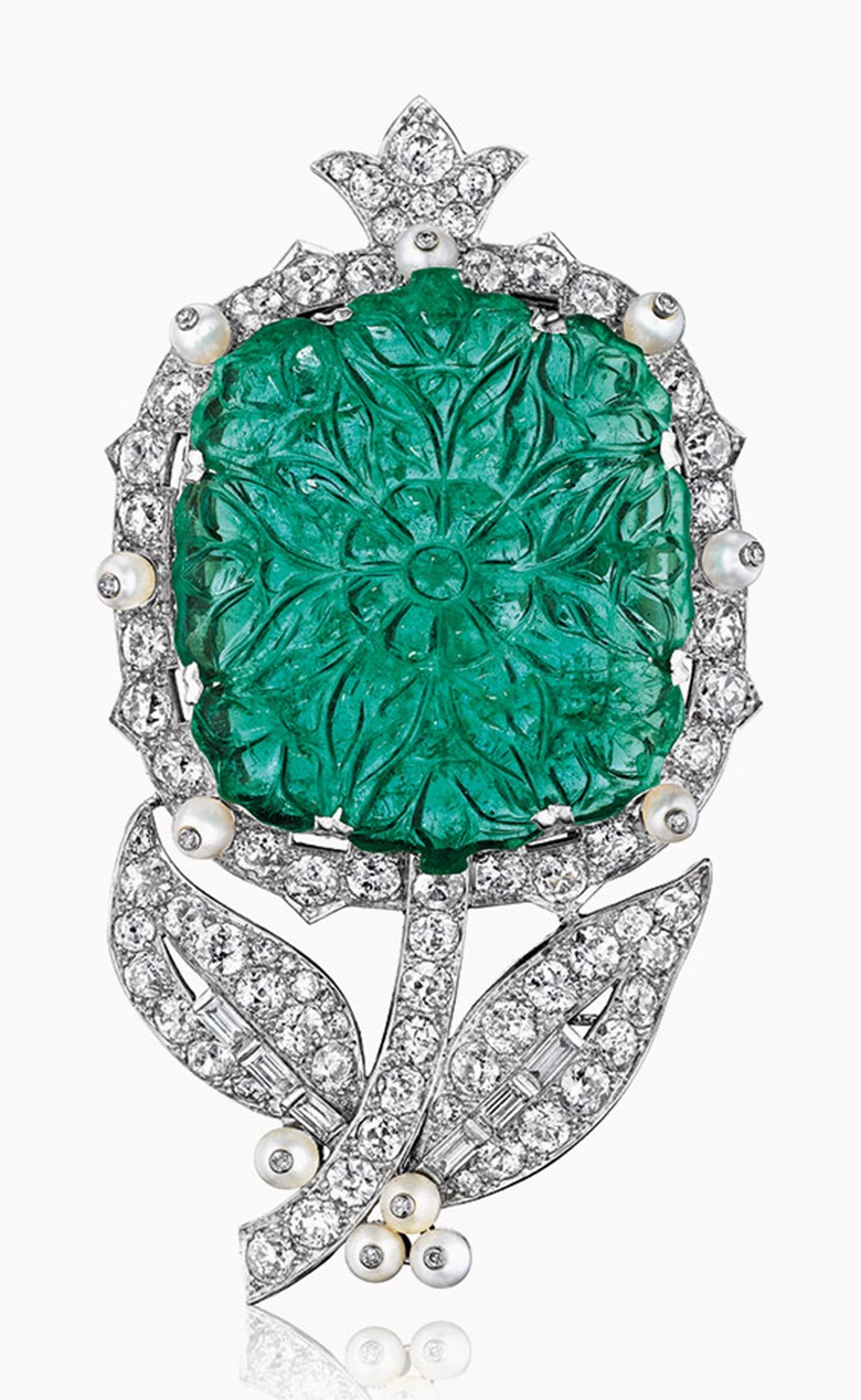 An emerald, pearl and diamond flower brooch, by Cartier. This lot was offered in Magnificent Jewels on 7 December 2016 at Christie's in New York and sold for $487,500
