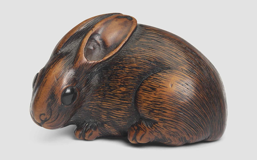 A wood netsuke of a hare. Signed on an oval reserve Hidari Issan, Iwashiro, Edo period (19th century). 4.5 cm long. This lot was offered in Art of Japan on 8 December 2016 at