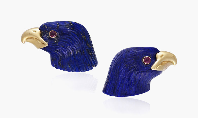 Verdura lapis lazuli and ruby eagle cufflinks, circa late 20th century. Each designed as a carved lapis lazuli eagle, set with a round ruby eye and a gold beak. Estimate $3,000-5,000. This lot is offered in Cufflinks for the Modern Gentleman, 1-13 December, Online