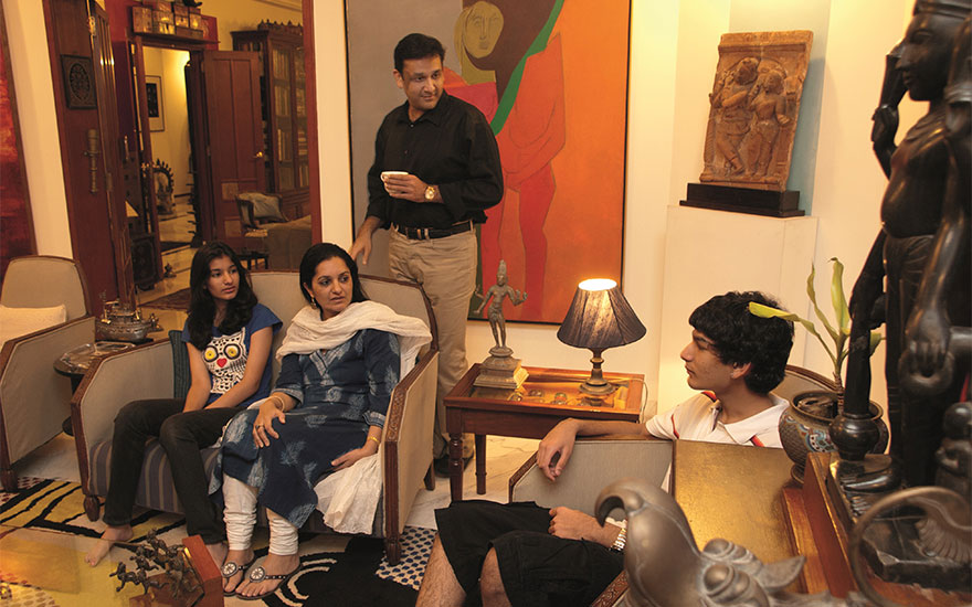 The Poddar family in their living room with Tyeb Mehta (1925-2009), Untitled (Diagonal), 1975, offered on 18 December in Mumbai. Photograph © Mahesh Bhat, image courtesy the Poddar family