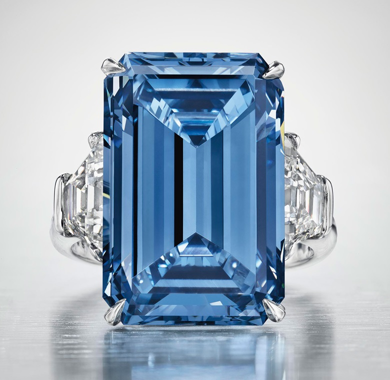 The Oppenheimer Blue, a sensational coloured diamond ring. Set with a Fancy Vivid Blue rectangular-cut diamond, weighing approximately 14.62 carats, flanked on either side by a trapeze-shaped diamond. Sold for CHF 56,837,000  $58,002,681 on 18 May 2016
