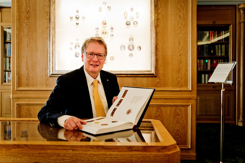 Dr. Friess with a copy of The Emergence of the Portable Watch, the catalogue of the Patek Philippe Museum