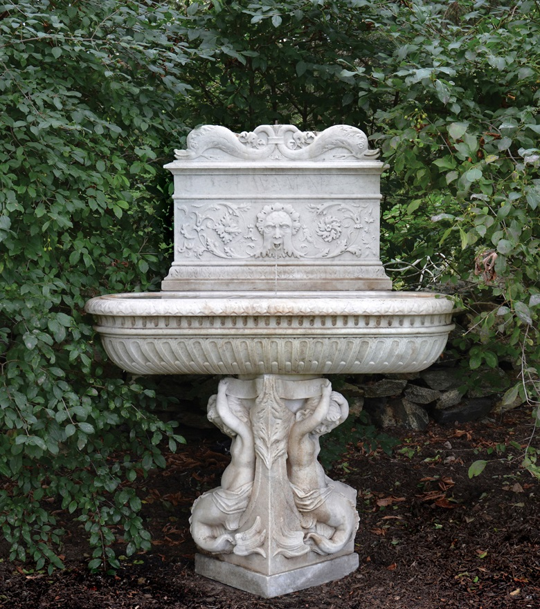 A composite antique stone fountain with 19th-century components in the front and a Renaissance marble slab at the back, circa 1485, engraved with dolphins, foliage and the words 'Lava Mini' ('Wash Your Hands'), at Barbara Israel Garden Antiques