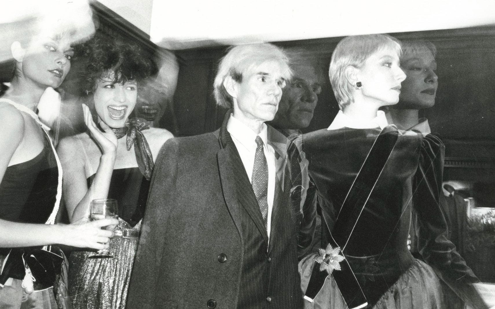 Andy Warhol (1928-1987), Andy Warhol and Models, 1982. Unique gelatin silver print, 8 x 10 in (20.3 x 25.4 cm). Estimate $5,000-7,000. This work is offered in Andy Warhol@Christie's with NYFW