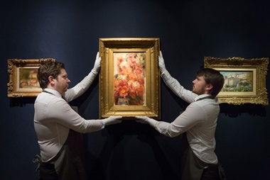 Christie's art handlers add the final touch to a wall displaying works by Renoir