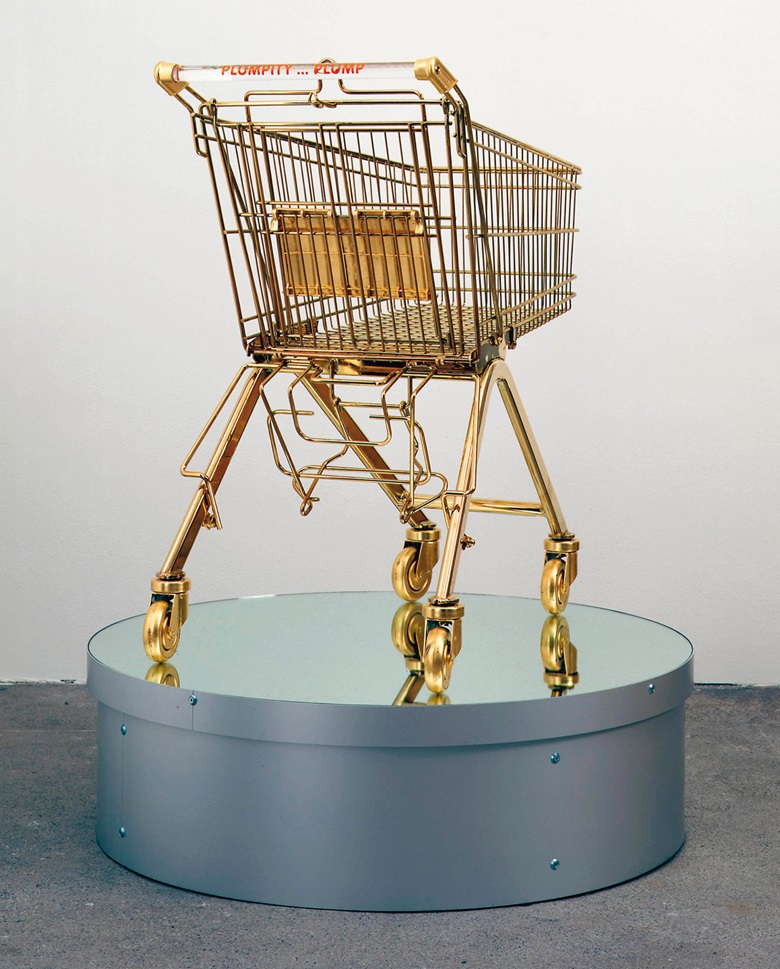 Sylvie Fleury (b.  1961), Serie Ela 75K (Plumpity...Plump), 2000. Gold-plated shopping cart, plexiglass handle, vinyl text and rotating pedestal, shopping cart 32⅝ x 37 ¾ x 21⅝ in (83 x 96 x 55 cm); overall 44⅞ x 39⅜ x 39⅜ in (114 x 100 x 100 cm). This lot was offered in First Open on 5 April 2017 at Christie's in London and sold for £20,000