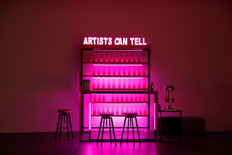 Wang Xin, Artists Can Tell, 2016. Table, chairs, signboard, LED lights, custom bottles, Kool Aid, vodka. 200 x 140 x 160 cm. Courtesy de Sarthe Gallery