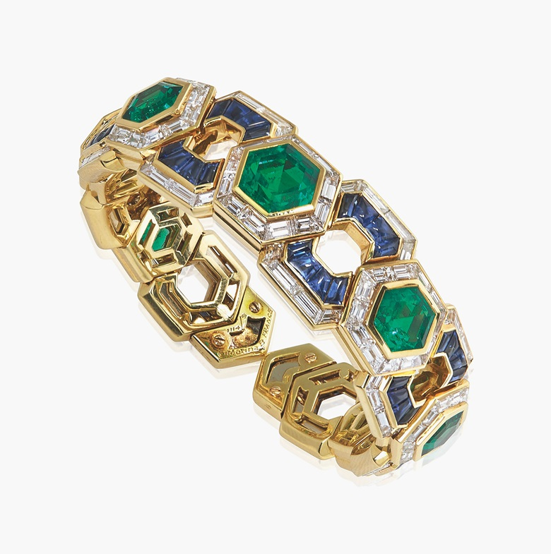 The unique emerald, sapphire and diamond 'Exi' bangle, by Marina B. The expandable cuff bracelet composed of seven hexagonal step-cut graduated emeralds within a baguette-cut diamond surround, to the buff-top sapphire and diamonds spacers, 1989, 14.5 cm inner circumference, with French assay mark for gold. Signed and with makers mark for Marina B, no. 11149. Estimate