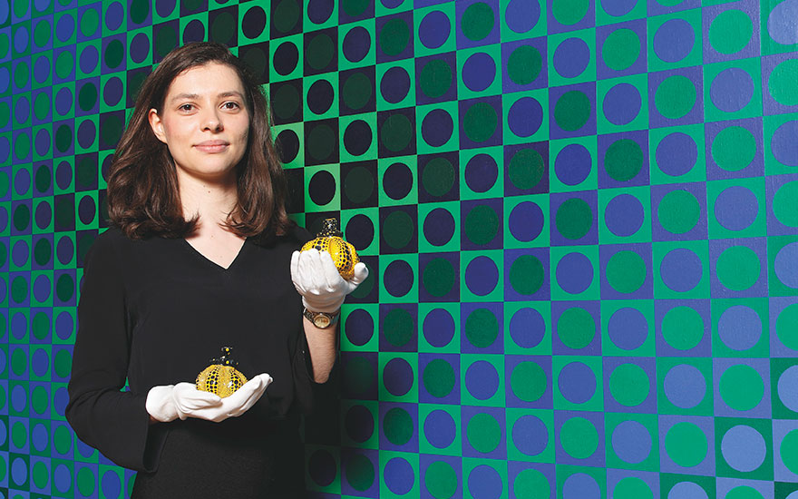 Specialist Victoria Gramm with two miniature masterpieces by Yayoi Kusama. Gramm stands beside Victor Vasarely (1906-1997), Boglar-I, 1966. Acrylic on canvas. 250 x 250cm. Estimate