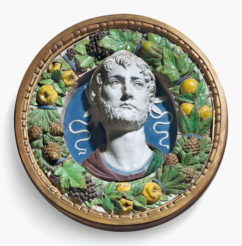 A polychrome-glazed terracotta bust of a laureate in a frame of fruit, vegetables and pine cones by Andrea della Robbia (1435-1525), Florence, circa 1487-1494, the frame, della Robbia workshops and associated. 16 in (41 cm) diameter the bust relief; 24½ in (62 cm) diameter of terracotta frame; 27⅓ (69.5 cm) diameter of giltwood frame. Estimate $200,000-400,000. This lot is offered in