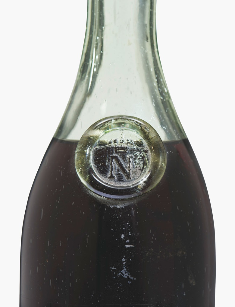 Napoléon Cognac 1811. 'N'-embossed glass shoulder-button. No label. Embossed short metal capsule states '1811 – Maison de L'Empereur – Chateau de Fontainebleau'. Original slightly shrunken cork. Level 6.5 cms below base of cork. 1 bottle. Estimate £4,000-6,000. This lot is offered in Interiors on 14 June 2017 at Christie's South