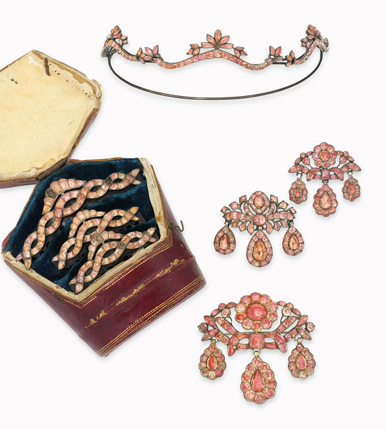 A group of late-18th-century Portuguese topaz jewellery. Comprising a bodice ornament and ear pendants of girandole design, a tiara, three hair combs and a crescent-shaped hair pin (not illustrated), each modelled as a scrolling ribbon with floral and foliate motifs entirely set with vari-cut topaz, foil-backed in silver, circa 1770. Estimate £15,000-20,000. This lot is offered