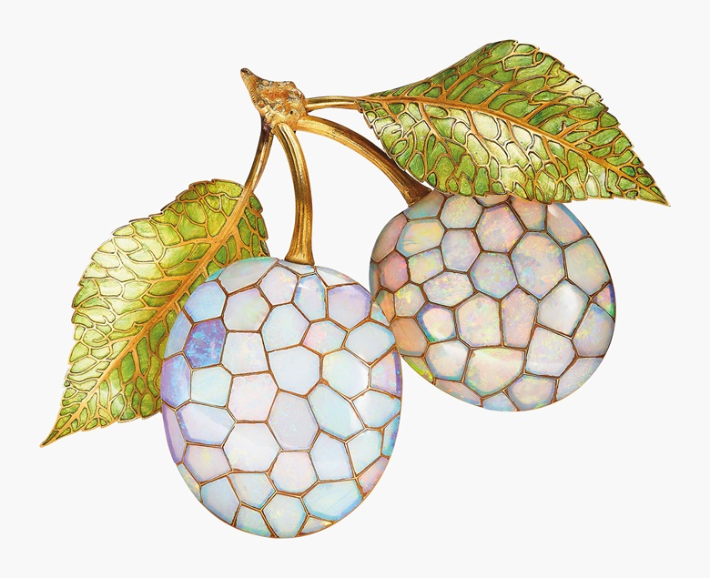 An Art Nouveau opal and enamel brooch, by René Lalique. Modelled as a naturalistic plum branch, the two plums set with geometric opal panels, to the textured gold stems and green enamel leaves, circa 1900. 11.0 cm, with French assay marks for gold, in René Lalique fitted case. Estimate CHF 90,000-130,000. This lot is offered in Beyond Boundaries Magnificent Jewels from a European