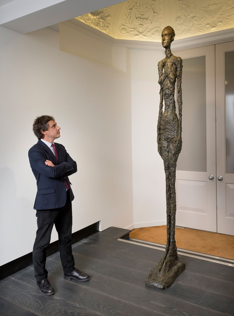 Pierre Martin-Vivier with Alberto Giacometti, Grand Femme II.  Bronze with dark brown patina. Height 108⅞ in (276.5 cm). Conceived in 1960; this bronze cast in 1980-81 © The Estate of Alberto Giacometti (Fondation Annette et Alberto Giacometti, Paris and ADAGP, Paris), licensed in the UK by ACS and DACS, London 2017