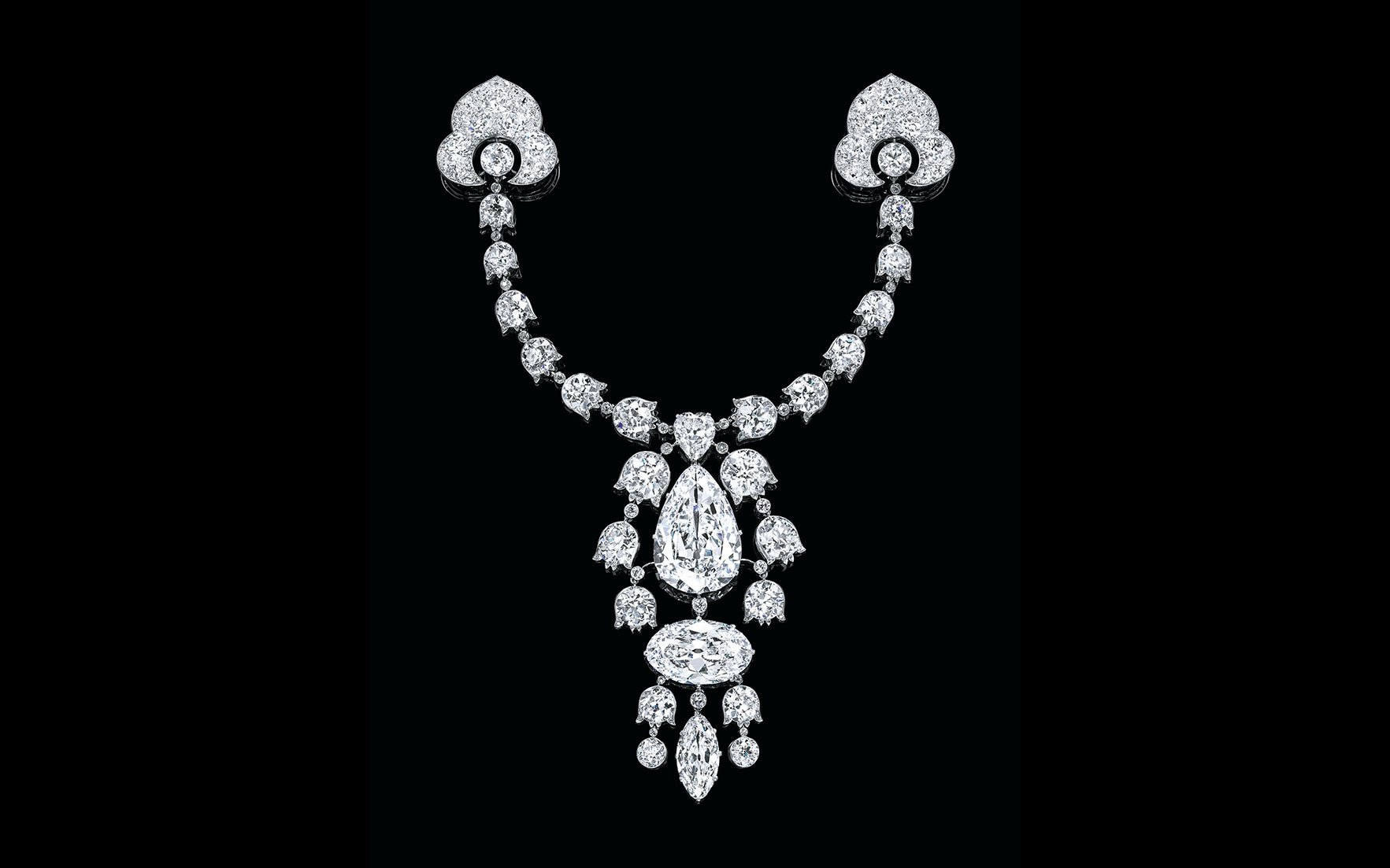 A Belle Epoque diamond devant-de-corsage brooch, by Cartier. The pendant centreing upon a pear-shaped diamond weighing 34.08 carats, and below a marquise-shaped diamond weighing 23.55 carats,