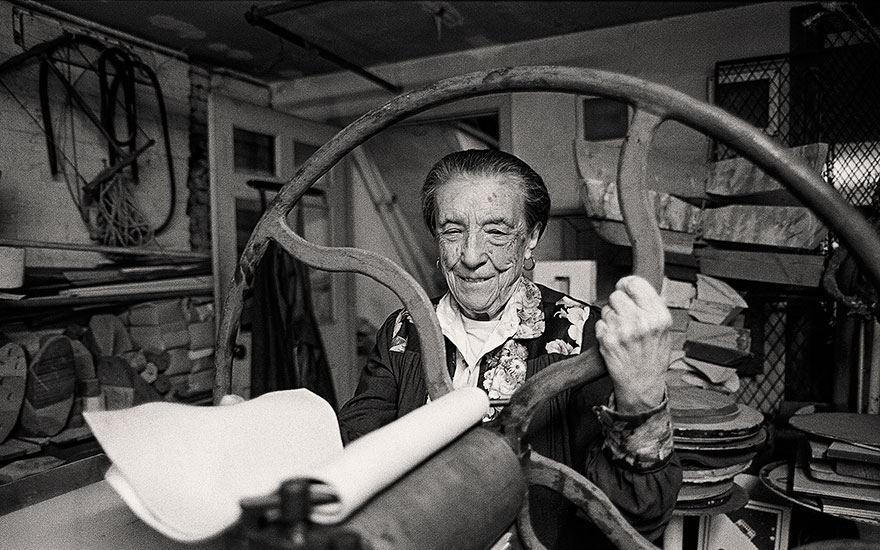 Louise Bourgeois at the printing press in the lower level of her home and studio on 20th Street, New York, 1995. Photograph by and © Mathias Johansson