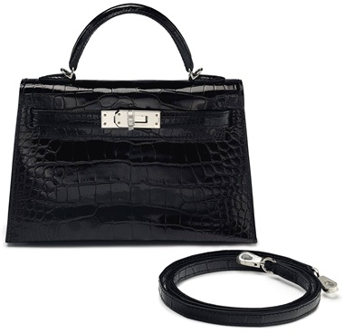 A shiny black alligator sellier mini kelly 20 ii with palladium hardware, Hermès, 2017. 20 w x 16 h x 10 d cm. Estimate $25,000-35,000. This lot is offered in Handbags & Accessories, 22 November to 5 December 2017, Online  Very few of these exotic mini Kellys still exist. Black is an evening wear staple, and its small size and crossbody option make it easy to manoeuvre.