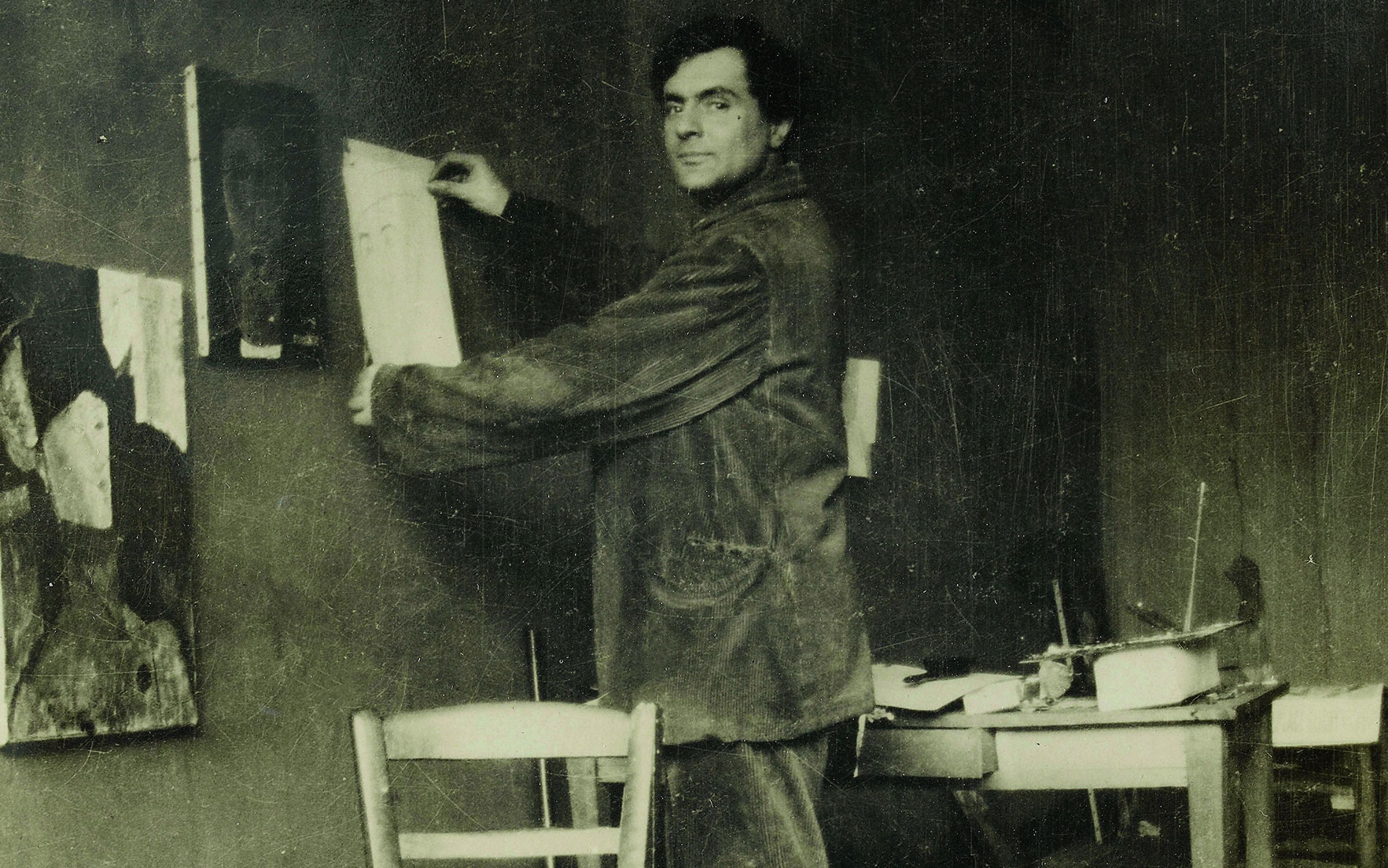 Modigliani in his studio. Photograph by Paul Guillaume, c. 1915 © RMN-Grand Palais (Musée de l'Orangerie) I Archives Alain Bouret, image Dominique Couto