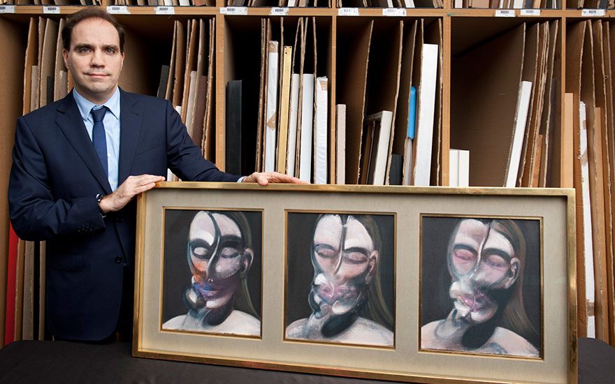 Francis Outred, Head of Post-War and Contemporary Art at Christie's, with Francis Bacons Three Studies for a Portrait  (1976) © The Estate of Francis Bacon. All rights