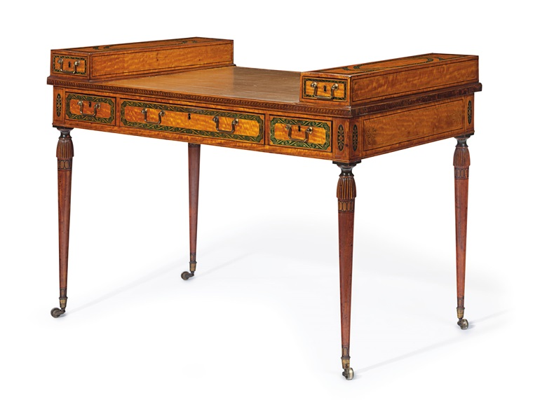 A late George III polychrome-painted satinwood ladys writing table, circa 1790-1800. 34 in (86 cm) high; 48 in (122 cm) wide; 27 in (69 cm) deep. Estimate $8,000-12,000. This lot is offered in The Collection of Peggy and David Rockefeller in Spring 2018 at Christie's in New York
