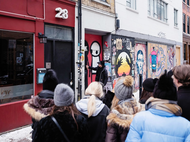 Stik touches up A Couple Hold Hands in the Street  on Brick Lane in London, to the delight of an onlooking crowd of Danish tourists