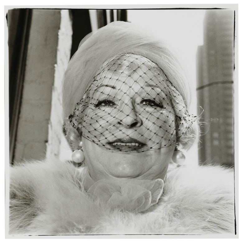 Diane Arbus (1923-1971), Woman with a veil on Fifth Avenue, New York City, 1968. Gelatin silver print, printed later by Neil Selkirk. Image 14¾ x 14⅝ in (37.5 x 37.1 cm). Sheet 19¾ x 15⅞ in (50.2 x 40.3 cm). This work is number 27 from an edition of 75. Estimate$12,000-18,000. This work is offered in The Comedians online auction, 5-10 April