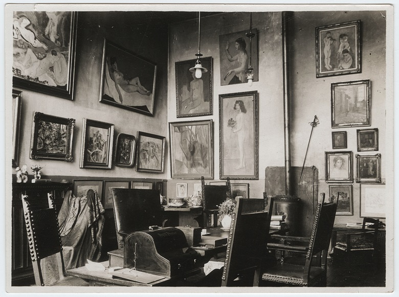 The Steins' Paris home, circa 1912-13. Picasso's Fillette à la corbeille fleurie, 1905, is to the left of the stove. Photo from the Gertrude Stein and Alice B. Toklas papers, Yale Collection of American Literature, Beinecke Rare Book and Manuscript Library, Yale University. Artworks © ADAGP, Paris and DACS, London 2018. © Succession H. MatisseDACS, London 2018. ©