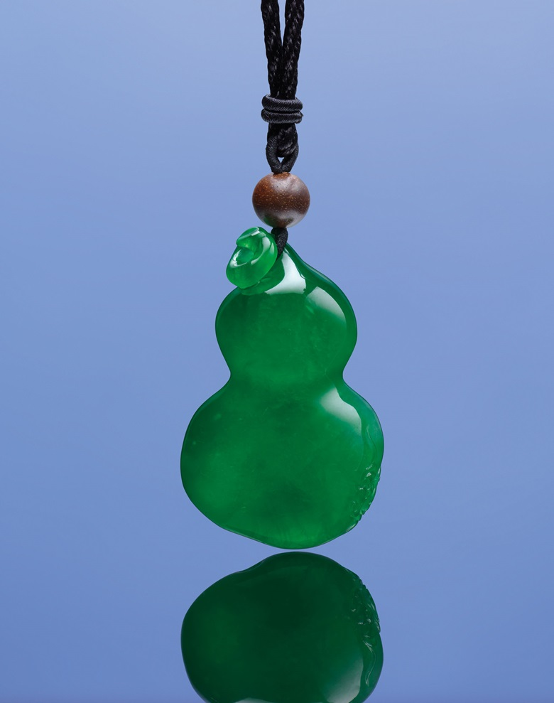 A jadeite hulu pendant necklace. Suspending a jadeite hulu carved with a pair of bats, to the wooden bead surmount and length adjustable black silk cord, carving approximately 59.1 x 35.6 x 16.4 mm. Estimate HK$18,000,000-28,000,000. Offered in Hong Kong Magnificent Jewels on 29 May at Christie's in Hong Kong