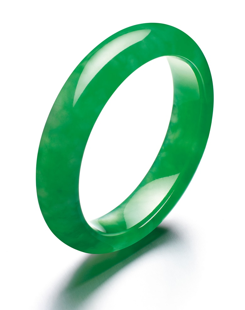 A superb jadeite bangle. The semi-cylindrical jadeite bangle of brilliant emerald green colour and high translucency, inner diameter approximately 53.7 mm, width approximately 13.8 mm, thickness approximately 8.2 mm. Sold for HK$40,440,000 on 27 May 2014 at Christie's in Hong Kong