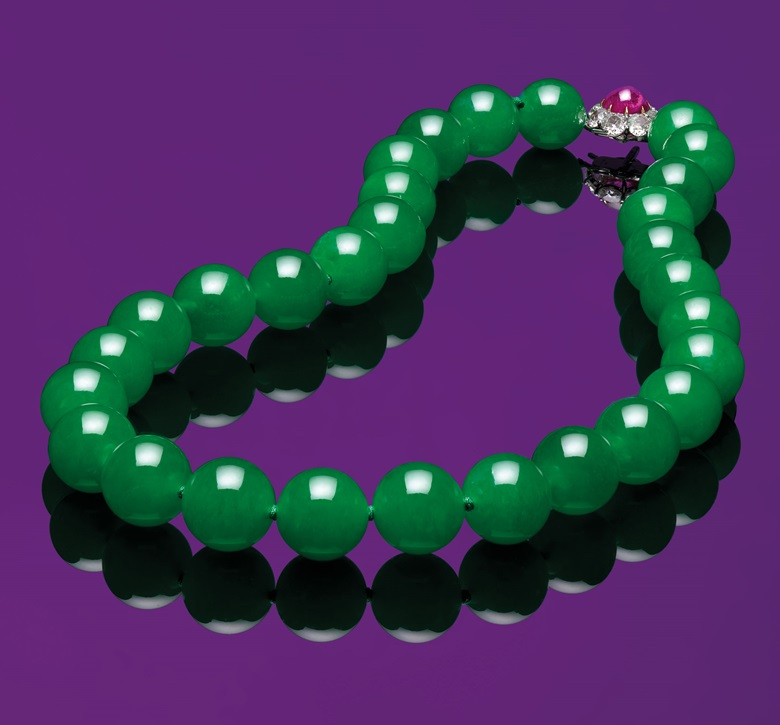 An extraordinary jadeite bead, ruby and diamond necklace. Composed of 29 graduated jadeite beads, measuring approximately 14.7 to 15.9 mm, to the cabochon ruby and old-cut diamond clasps, mounted in gold, 48.0 cm. Sold for HK$95,725,000 on 28 November 2017 — Christie's auction record for a jadeite bead necklace