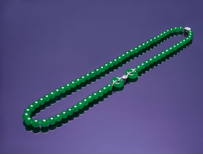 A jadeite and diamond necklace. Composed of 69 jadeite beads, measuring approximately 8.2 to 10.8 mm, spaced by a pair of jadeite hoops and an oval-shaped diamond, weighing approximately 1.50 carats, to the similarly-cut diamond clasp, weighing approximately 3.02 carats, mounted in platinum, the largest hoop diameter approximately 18.6 mm, thickness approximately 6.8 mm, necklace 73.5 cm. Estimate