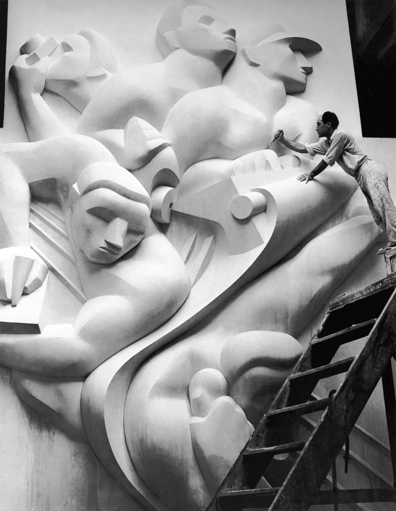 Isamu Noguchi working on the Associated Press Building plaque, which was carved in plaster and cast in stainless steel — then the largest-ever stainless-steel casting, 1940. Credit Underwood Archives Getty Images. Artwork © The Isamu Noguchi Foundation and Garden MuseumARS, New York and DACS, London 2018