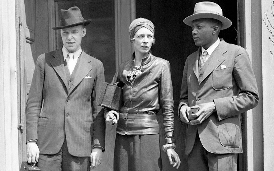 Nancy Cunard with John Banting, artist (left) and Taylor Gordon, writer (right) in front of the Grampian Hotel in Harlem, then her home, on  3 May, 1943. Nancy Cunard had told how her mother
