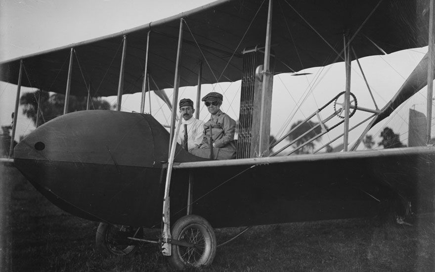 Katharine Wright, wearing a leather jacket, cap, and goggles, aboard the Wright Model HS airplane with Orville, 1915. Wright Brothers Negatives, Library of Congress Prints and Photographs Division