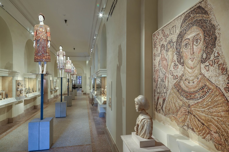 The Mary and Michael Jaharis Galleries for Byzantine Art. The dress on the first mannequin is by Domenico Dolce and Stefano Gabbana for Dolce & Gabbana, ensemble, autumnwinter 2013-14. On the right a fragment of a Byzantine floor mosaic with a personification of Ktisis, 500-550, said to have inspired Docle & Gabbana's creation. Image © The Metropolitan Museum of Art