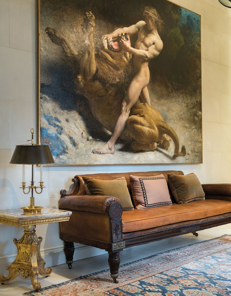The hallway at the Eaton Square residence, with a painting by Léon Joseph Bonnat, Samson's Youth (Estimate £250,000-350,000) and a George IV sofa (£3,000-5,000). The Directoire ormolu Bouillotte lamp (£4,000-6,000) sits on an Italian marble specimen table top on a William IV base  (£3,000-5,000). Offered in Rooms as Portraits Michael S. Smith, Eaton Square,