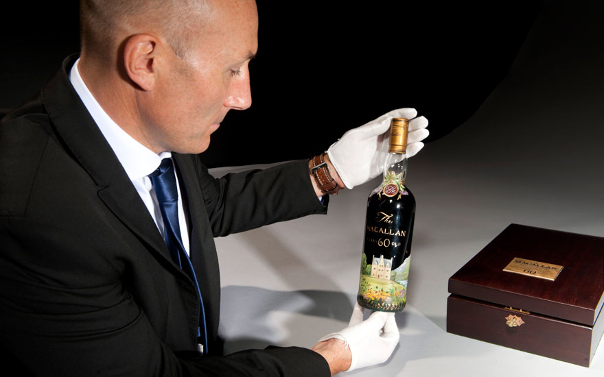 Tim Triptree MW, Christie's International Director of Wine, with a hand-painted bottle of The Macallan that set a new world auction record