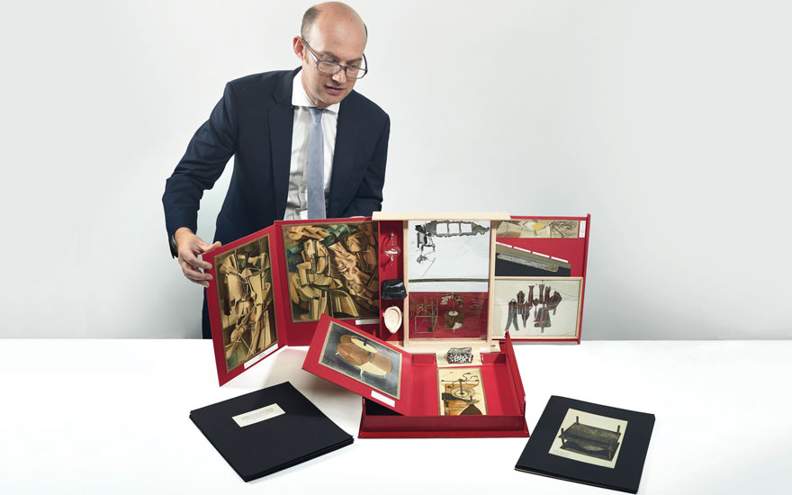 Tudor Davies unfolds the Boîte-en-valise  to reveal some of the miniature artworks within