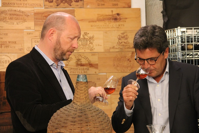 Edwin Vos of Christie's (left) and Francisco Albuquerque, Winemaker for the Blandys Madeira Wine Company, sample the Madeira from one of the 1820s demijohns