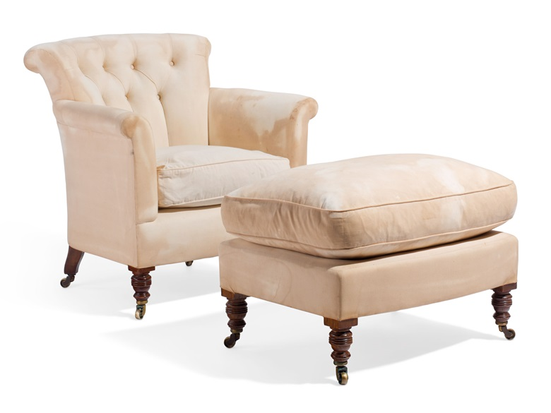 A 19th-century Howard & Sons club chair and ottoman in serious need of rejuvenation