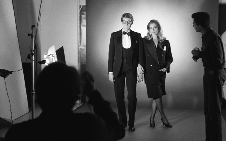 Catherine Deneuve, wearing a black wool smoking jacket and trousers by YSL, poses with Yves Saint Laurent in a shoot by photographer Helmut Newton (foreground left), 16 November 1981. The shoot