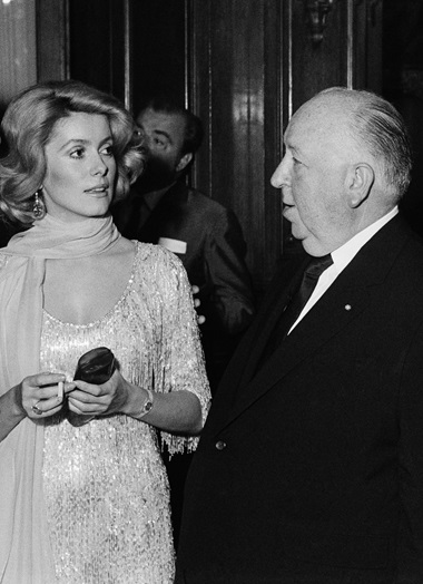 Catherine Deneuve, in a beaded evening dress from YSL's SpringSummer 1969 couture show, meets Alfred Hitchcock in 1969. Photograph Getty Images