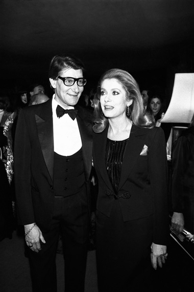 Catherine Deneuve and Yves Saint Laurent at the 20th anniversary celebrations of YSL at the Lido in Paris in 1982. Photograph Getty Images