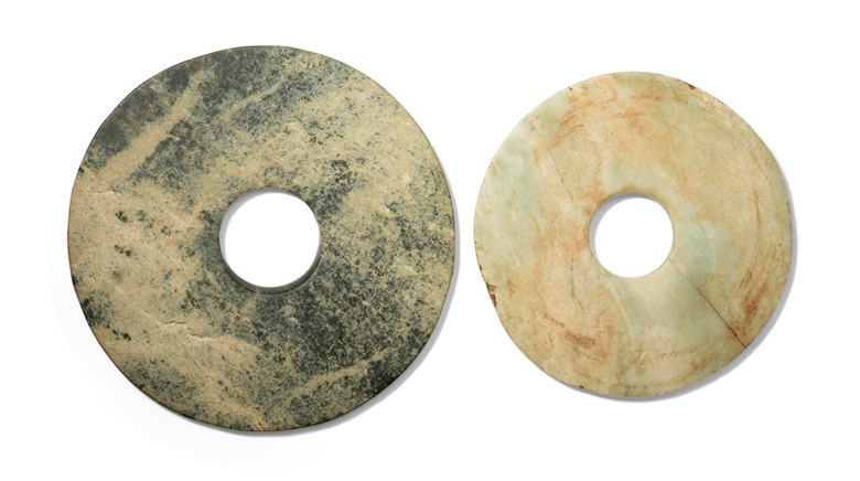 Two jade bi  discs, Neolithic Period (circa 6500-1700 BC). 7⅛ in (18 cm) diameter of the larger disc. Estimate £2,000-3,000. Offered in The Art of China Including Private English Collections, online, 14-21 February