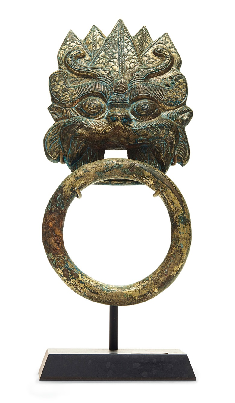 A gilt-bronze taotie mask and loose-ring handle, China, six dynasties period (ad 222-589). 7¾  in (19.7  cm) high overall, metal stand. Sold for $11,875 on 21 March 2019 at Christie's in New York