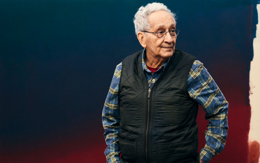 Frank Stella photographed at his home in front of Jules Olitskis 1964 work Hot Ticket (detail), 2019. Photo Christopher Gregory  New York Times  Redux  eyevine. Artwork © Estate of Jules OlitskiVAGA