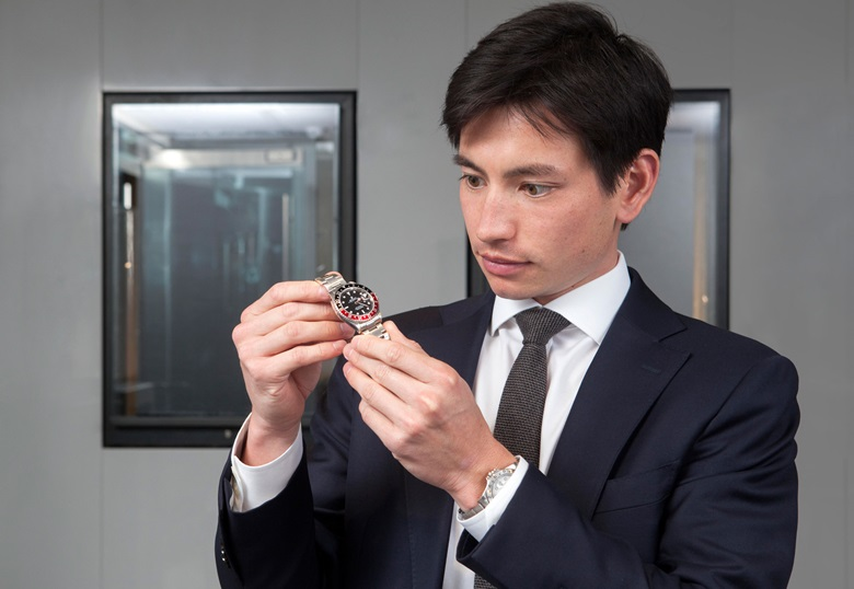 Ryan Chong inspects a Rolex GMT-Master with a 'Coke' colour-blocked bezel