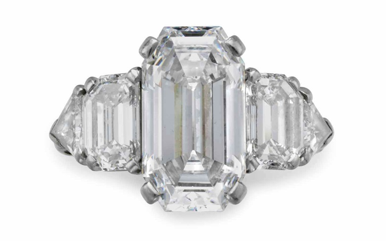 In 1940 David Rockefeller purchased this ring set with a cut-cornered rectangular step-cut diamond, weighing approximately 5.63 carats, with epaulet and triangular-cut diamond shoulders, from Raymond Yard. He presented the ring to Peggy McGrath upon their engagement. In 1959 the ring was returned to Raymond Yard, who altered the design, integrating additional diamonds on either side of the centre