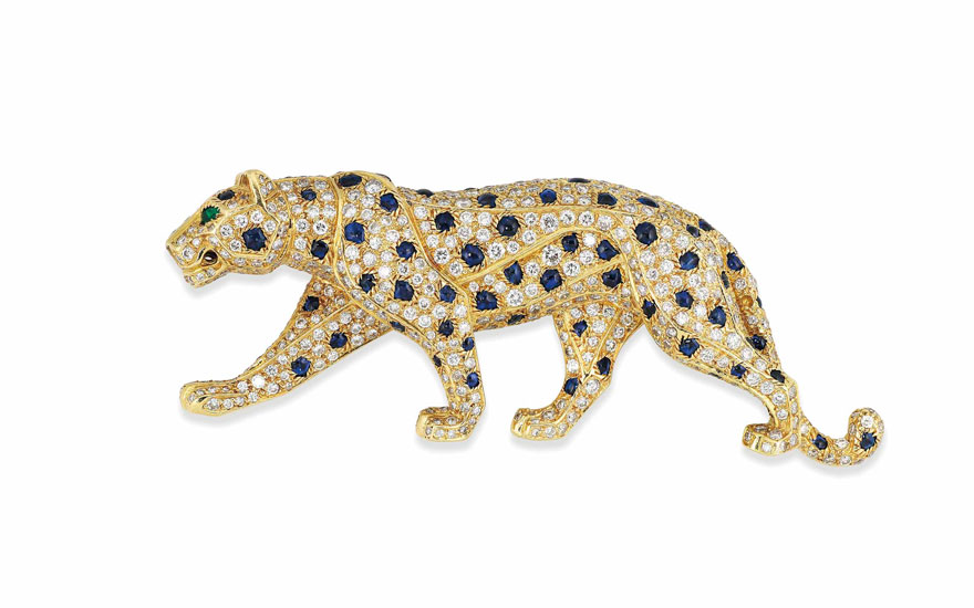 A sapphire and diamond Panthere Brooch, by Cartier. Pavé-set with brilliant-cut diamonds interspersed with buff-top sapphire spots, pear shaped emerald eyes and onyx nose detail, 6.4cm. Sold